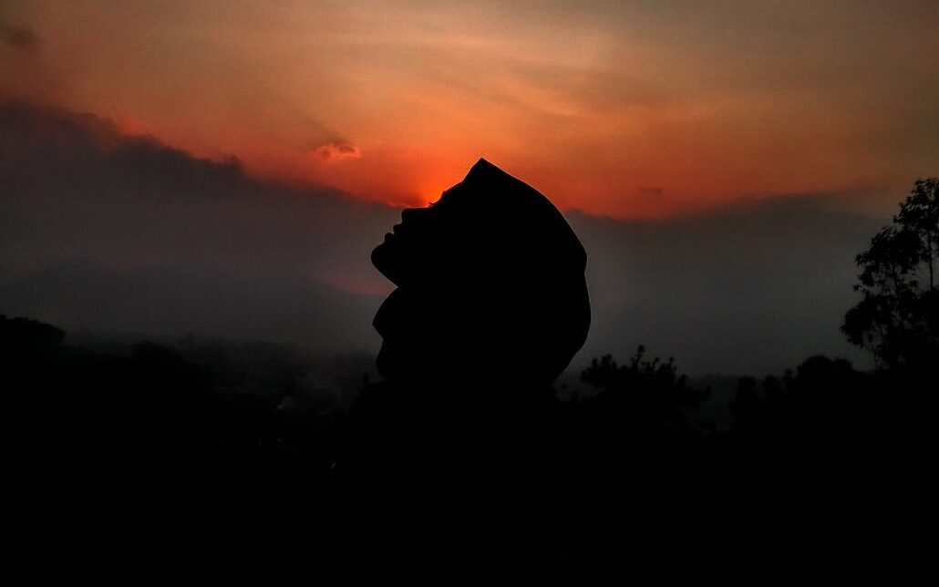 silhouette of person against sunset sky